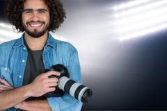 Lächelnder Mann mit Kamera auf seinen Händen auf Scheinwerferhintergrund Lizenzfreies Stockbild
