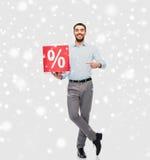 Lächelnder Mann mit rotem Prozentsatz unterzeichnen vorbei Schnee Lizenzfreie Stockfotos