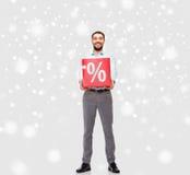 Lächelnder Mann mit rotem Prozentsatz unterzeichnen vorbei Schnee Stockfoto