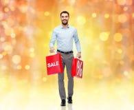 Lächelnder Mann mit roter Einkaufstasche Lizenzfreie Stockfotos