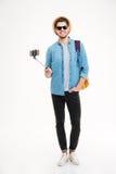 Lächelnder Mann mit Rucksack und Handy auf selfie haften Stockbild