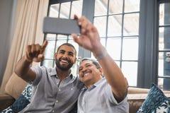 Lächelnder Mann mit seinem Vater, der zu Hause selfie nimmt lizenzfreie stockfotos
