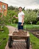 Lächelnder Mann mit Spaten und Gartenschubkarre Stockbild