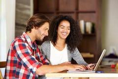 Lächelnder Mann und Frau, die mit Laptop arbeiten Stockfoto
