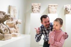 Lächelnder Mann und Tochter, die alte Statuen schauen Lizenzfreie Stockfotografie