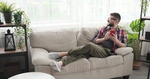 L?chelnder Mann unter Verwendung des Handys auf Sofa stock video