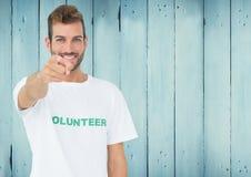Lächelnder Mannesfreiwilliger, der auf Kamera zeigt stockbilder