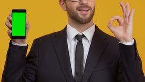 Lächelnder Mannvertretungs-O.K.zeichen-Holding Smartphone mit grünem Schirm, einfaches Bankwesen stock footage