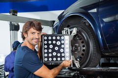 Lächelnder Mechaniker Adjusting Alignment Machine auf Auto Lizenzfreies Stockfoto