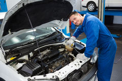 Lächelnder Mechaniker, der an Auto arbeitet Lizenzfreie Stockfotografie