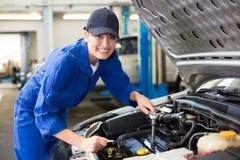 Lächelnder Mechaniker, der an Auto arbeitet Lizenzfreie Stockfotos