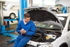 Lächelnder Mechaniker, der Auto betrachtet Stockfotografie