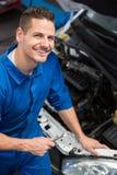 Lächelnder Mechaniker, der oben Kamera betrachtet Lizenzfreie Stockfotos