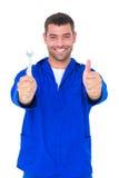 Lächelnder Mechaniker, der Schlüssel beim Daumen oben gestikulieren hält Stockbild