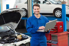 Lächelnder Mechaniker, der seinen Laptop verwendet Lizenzfreie Stockfotos