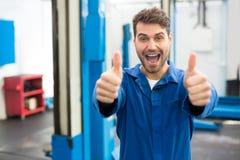 Lächelnder Mechaniker, der sich Daumen zeigt Lizenzfreies Stockfoto
