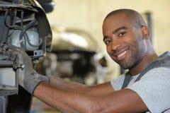 Lächelnder Mechanikerfestlegungsautomotor in der Garage Lizenzfreies Stockbild