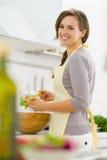 Lächelnder mischender Salat der jungen Hausfrau in der Küche Stockfoto