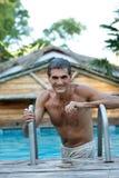 Lächelnder Mitte gealterter Mann, der im Pool steht Stockfotos