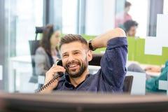 Lächelnder mittlerer erwachsener Geschäftsmann, der am Telefon im Büro spricht Stockfotos