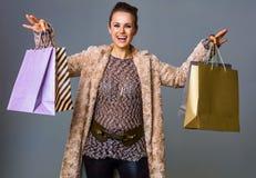 Lächelnder Modehändler lokalisiert auf dem Grau, das Einkaufstaschen zeigt Stockbilder