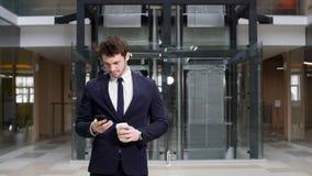 Lächelnder moderner junger Geschäftsmann, der am Telefon beim Gehen spricht stock video footage