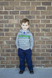 Lächelnder netter Junge, der sich gegen eine Backsteinmauer wehrt Stockbilder