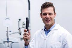 Lächelnder Optometriker, der Ophthalmoskop hält Lizenzfreie Stockfotografie