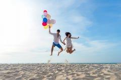 Lächelnder Paarhandholdingballon und zusammen springen und Glückwunschstaffelung in guten Rutsch ins Neue Jahr 2019 auf dem Stran stockbilder