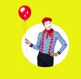 Lächelnder Pantomime mit Ballon Lustiger Schauspieler im roten Barett Stockbilder