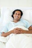 Lächelnder Patient, der auf einem Krankenhausbett liegt Lizenzfreies Stockbild