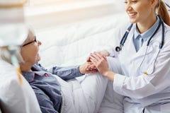 Lächelnder Patient, der Hand von Doktor hält stockbild