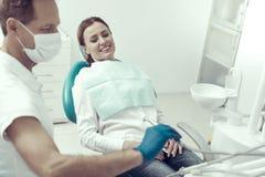 Lächelnder Patient, der nicht in einem zahnmedizinischen Kabinett gesorgt schaut lizenzfreies stockfoto
