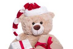 Lächelnder Porträtteddybär tragender Weihnachtshut mit Geschenk boxe Lizenzfreie Stockfotografie