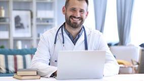 Lächelnder positiver Doktor At Work Looking an der Kamera stock footage