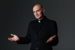Lächelnder Priester, der Sie steht und einlädt stockfoto