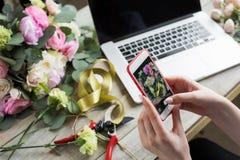 Lächelnder reifer Frauen-Floristen-Small Business Flower-Ladenbesitzer Sie benutzt ihr Telefon und Laptop, um Bestellungen für en Stockfotografie