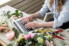 Lächelnder reifer Frauen-Floristen-Small Business Flower-Ladenbesitzer Sie benutzt ihr Telefon und Laptop, um Bestellungen für en Stockbild