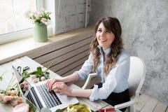 Lächelnder reifer Frauen-Floristen-Small Business Flower-Ladenbesitzer Sie benutzt ihr Telefon und Laptop, um Bestellungen für en Lizenzfreie Stockbilder
