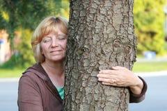Lächelnder reifer Frauenarm um Baum Lizenzfreie Stockbilder