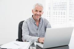 Lächelnder reifer Geschäftsmann unter Verwendung des Laptops am Schreibtisch im Büro Stockfotos