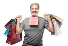 Lächelnder reifer Mann, der Einkaufstaschen lokalisiert auf Weiß hält Lizenzfreies Stockbild