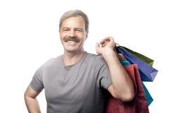 Lächelnder reifer Mann, der Einkaufstaschen lokalisiert auf Weiß hält Lizenzfreie Stockbilder