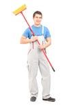 Lächelnder Reiniger in einer Uniform mit einem Besen Stockbilder