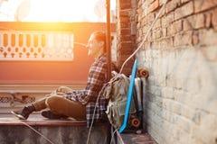 Lächelnder Reisender bemannen das Sitzen am Rand des Dachs und hörende Musik in den Kopfhörern mit Rucksack und Skateboard Lizenzfreie Stockfotografie