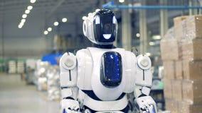 Lächelnder Roboter geht vorwärts in Fabrikvoraussetzungen stock footage
