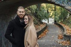 Lächelnder Rothaarigemann und nette blonde Frau unter alter Brücke bilden einen Bogen Lizenzfreies Stockbild