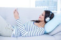 Lächelnder schöner Brunette, der auf der Couch und der hörenden Musik beim Nehmen von selfie sich entspannt Stockfotos