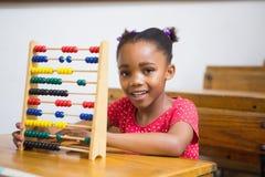 Lächelnder Schüler, der Abakus im Klassenzimmer verwendet Stockfotografie