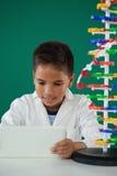 Lächelnder Schüler, der digitale Tablette im Labor verwendet Stockbilder